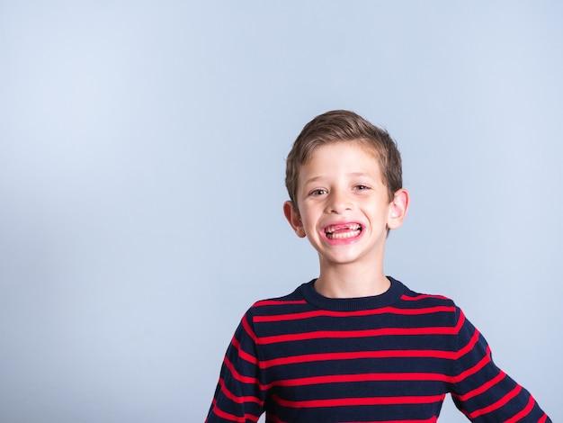 前歯が欠けている7歳の少年の肖像画、灰色の背景で隔離、コピースペース
