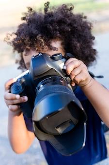 공원에서 전문 카메라를 가지고 노는 아프리카계 미국인 아기의 초상화.