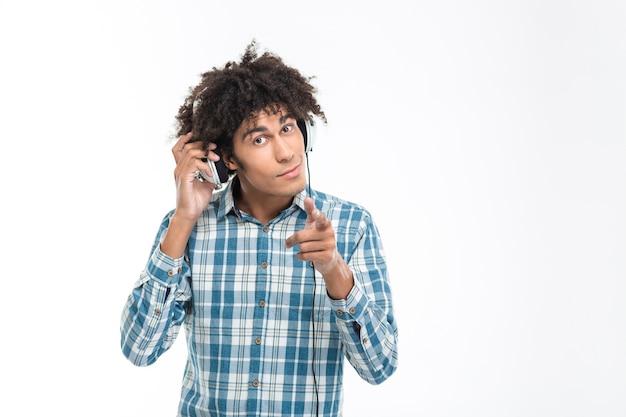 아프리카 계 미국인 남자 헤드폰에서 음악을 듣고 흰 벽에 고립 가리키는 손가락의 초상화