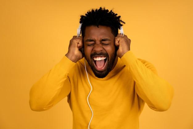 孤立した黄色の背景に立ってヘッドフォンで音楽を聴いて楽しんでいるアフロ男の肖像画。