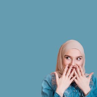 青い背景に驚く女性の肖像画