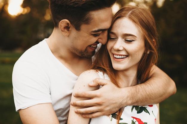 남자가 그들의 휴가 시간에 데이트하는 동안 일몰에 빨간 머리를 가진 그녀의 여자 친구를 뒤에서 포용하는 동안 웃고있는 놀라운 부부의 초상화.