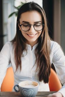 여행하는 동안 커피를 마시는 커피 숍에 앉아있는 동안 웃는 아래를 내려다 보면서 눈 안경을 쓰고 놀라운 장발 여자의 초상화.