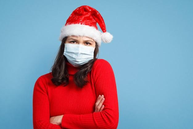 Портрет встревоженной женщины в красной рождественской шапочке и защитной медицинской маске.