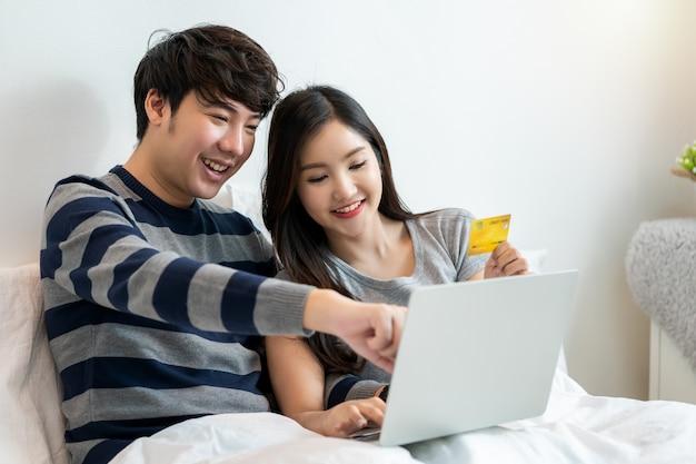 집에서 침대에 앉아 노트북 컴퓨터로 인터넷에서 쇼핑하는 아시아의 쾌활한 커플 초상화