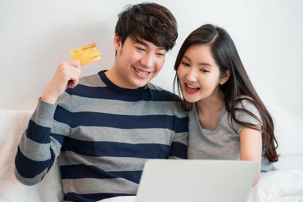 집에서 침대에 앉아있는 동안 랩톱 컴퓨터와 인터넷에서 온라인 쇼핑 아시아 명랑 커플의 초상화