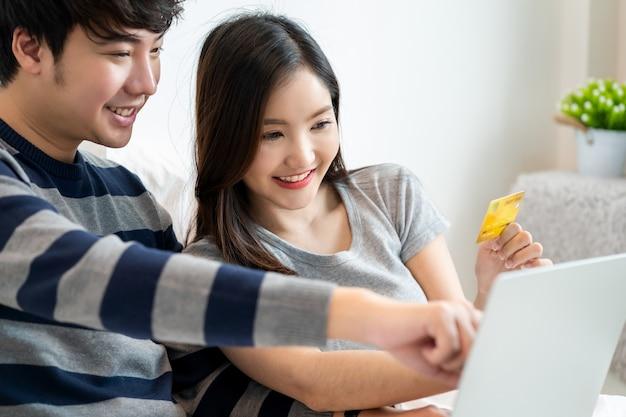 노트북 컴퓨터로 인터넷에서 온라인 쇼핑을 하는 쾌활한 아시아 커플의 초상화