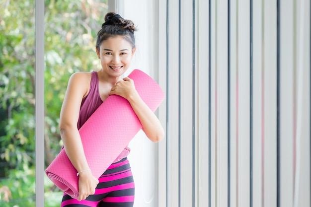 Портрет йоги азиатской разминки женщин практикуя в розовом платье обнимает пинк крена циновки йоги и практикует образ жизни здоровья раздумья и концепцию фитнеса здоровья в спортзале.