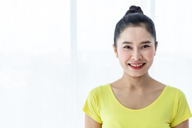 黄色のドレスでヨガを練習し、ジムで瞑想ウェルネスライフスタイルと健康フィットネスの概念を練習するアジアの女性のトレーニングの肖像画。