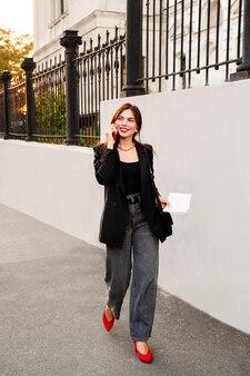 魅力的な幸せな女の子の肖像画は、携帯電話で話し、笑顔です