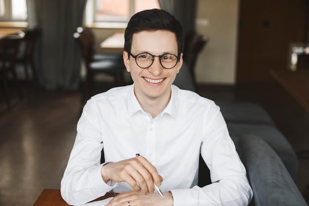 메모를 깨어 커피 숍에서 책상에 앉아 웃 고 멀리보고 흰 셔츠와 안경을 착용하는 매력적인 긍정적 인 관리자의 초상화.