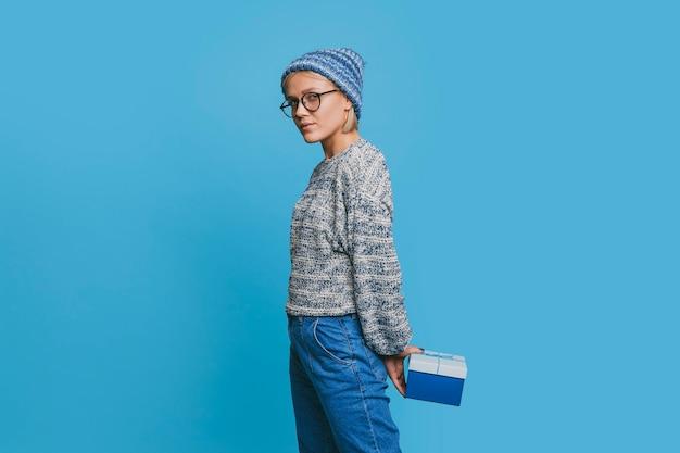 Портрет привлекательной молодой блондинки женщины, одетой в синий, глядя на камеру серьезно, держа синюю подарочную коробку в изоляции на синем.