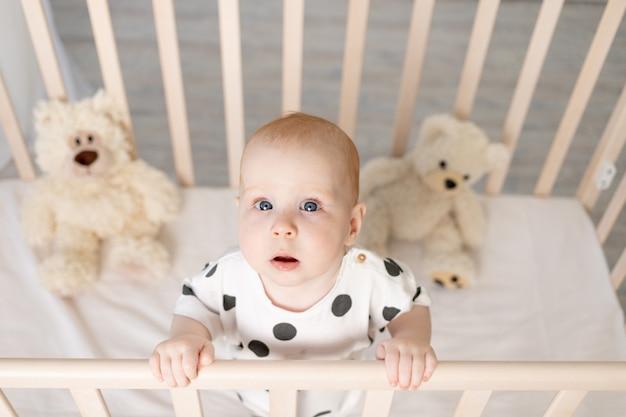 寝て、カメラ、テキストのための場所を見た後、明るい子供部屋のパジャマのおもちゃでベビーベッドに立っている8ヶ月の赤ちゃんの肖像画