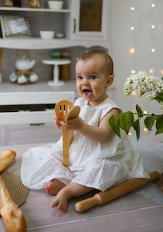 テーブルの上に座って、木製のシャベルで遊ぶ白い綿のドレスを着た女の赤ちゃんの肖像画