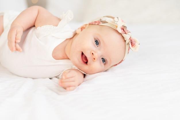 집에서 하얀 면 침대에 누워 웃거나 웃고 있는 여자 아기의 초상화