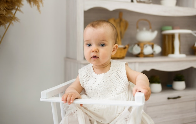 부엌에 앉아 카메라를 보고 있는 백인 어린이 의자에 파란 눈을 가진 여자 아기의 초상화