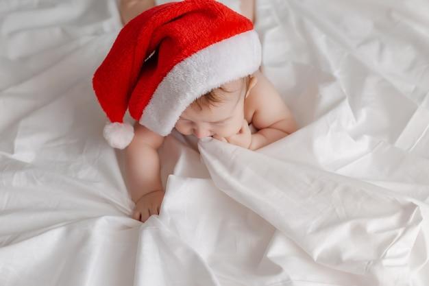 Портрет младенца в подгузниках, трусиках и шапке деда мороза, лежащего на животе на белой простыне