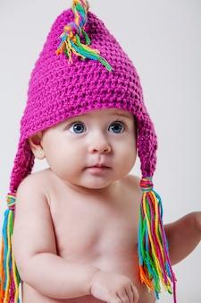 ピンクのウールの帽子とフリンジ付きの赤ちゃんの肖像画