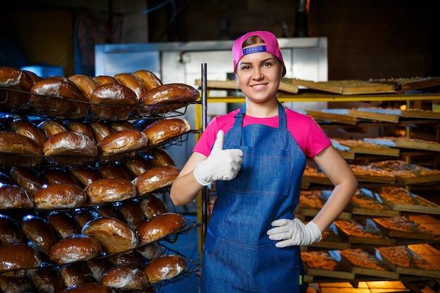 パン屋の焼きたてのパンと棚の背景にパン屋の女の子の肖像画。工業用パンの生産