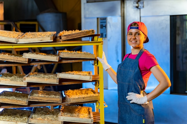 Портрет девушки пекаря с хлебом в руке на фоне линии в пекарне. промышленное производство хлеба