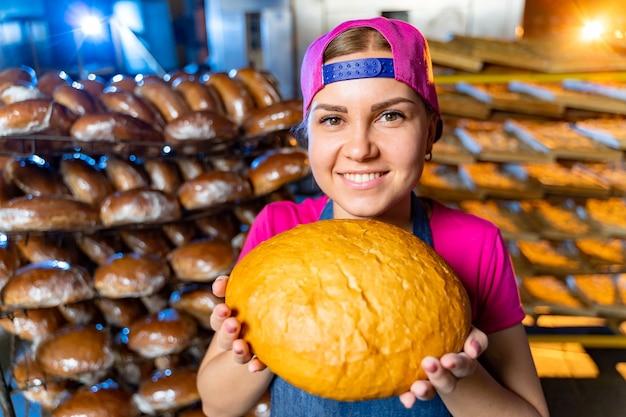 パン屋のラインの背景にパンを手にパン屋の女の子の肖像画。工業用パンの生産