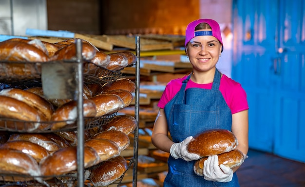 Портрет девушки пекаря с хлебом в руках на фоне линии в пекарне. промышленное производство хлеба