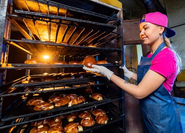 パン屋のラインの背景に熱い甘いパンを手に持っているパン屋の女の子の肖像画。工業用パンの生産