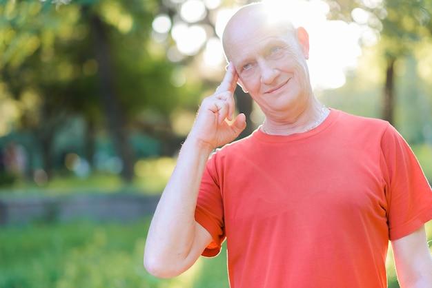 Портрет лысого мужчины в красной футболке, задумчивое выражение лица, держащего палец у виска