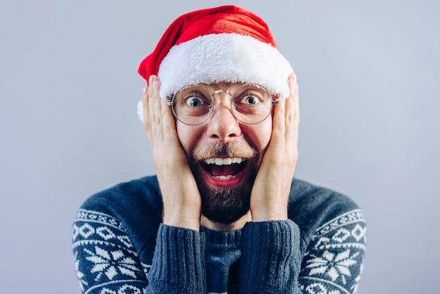 Портрет бородатого парня в новогодней шапке и очках с изумлением