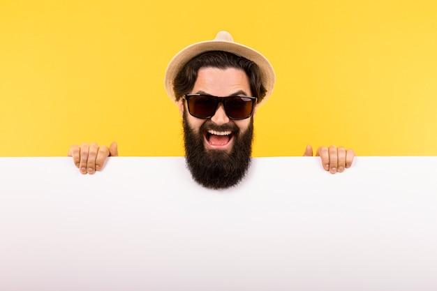 Портрет бородатого парня в солнечных очках и панамской шляпе, мужчина держит белое знамя, летний рекламный щит