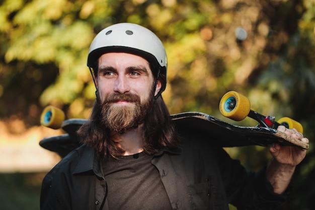 スケートボード、ロングボードを手にしたひげを生やした男の肖像画。高品質の写真