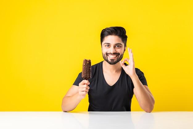 Портрет бородатого красивого индийского молодого человека, едящего мороженое в рожке или эскимо, сидя за столом на желтом студийном фоне