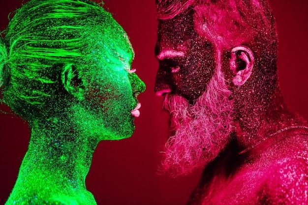 ひげを生やした男性と女性の肖像画は、紫外線パウダーで描かれています。