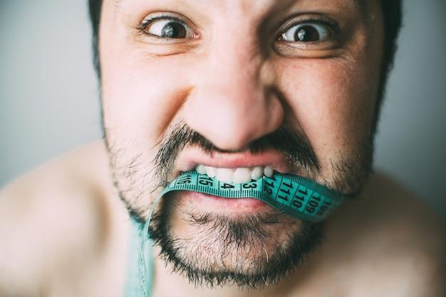 スタジオで撮影する巻尺の歯を握りしめているひげを生やした男の肖像