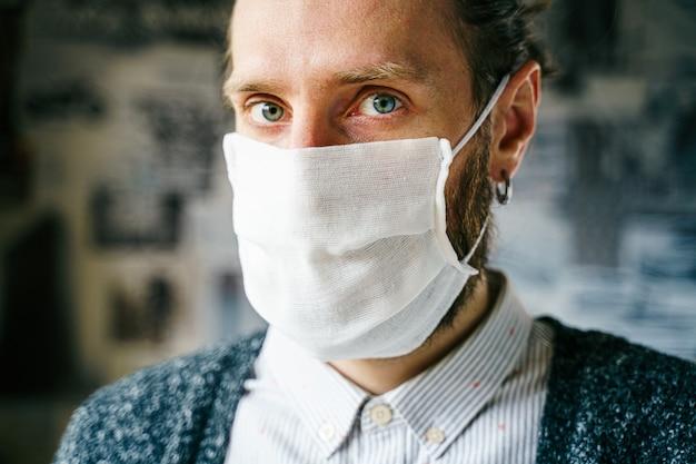 ガーゼマスクのひげを生やした男の肖像画。ウイルス感染からあなた自身の健康を予防的に保護します。コロナウイルスの概念。