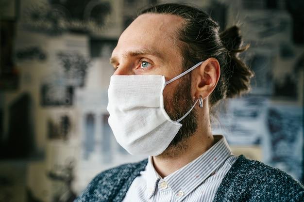 ガーゼマスクのひげを生やした男の肖像画ガーゼマスクのひげを生やした男の肖像画。ウイルス感染からあなた自身の健康を予防的に保護します。コロナウイルスの概念。