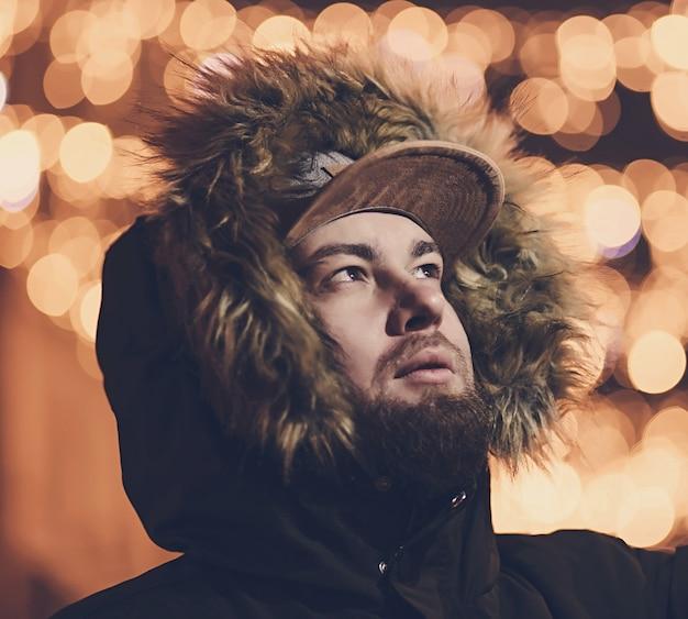街の明かりに対して冬のジャケットを着たひげを生やした男の肖像画