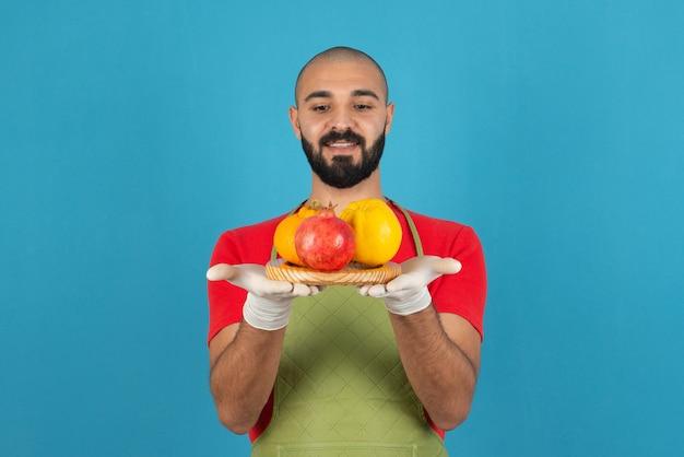 Портрет бородатого мужчины в фартуке, держащего деревянную доску свежих фруктов.
