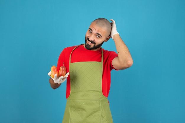 Портрет бородатого мужчины в фартуке, держащего свежие груши у синей стены.