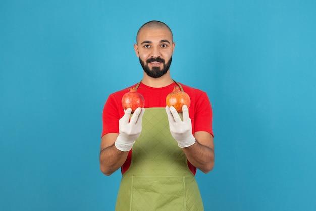 Портрет бородатого мужчины в фартуке, держащего в руках два свежих граната.