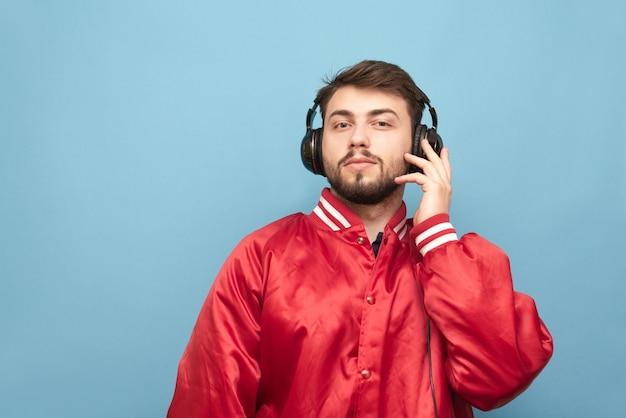 Портрет бородатого мужчины в наушниках и красной куртке на синем
