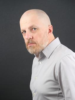 Портрет бородатого мужчины на серой поверхности