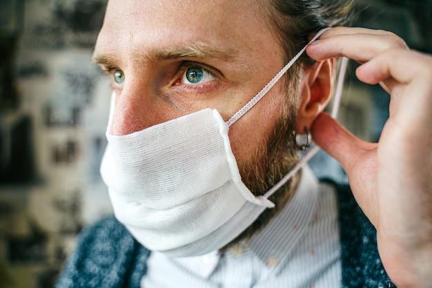 あごひげを生やした男の肖像画は、家を出る前にガーゼマスクを着用します。ウイルス感染に対する予防的戦い-コロナウイルスcovid-19。健康保護の概念