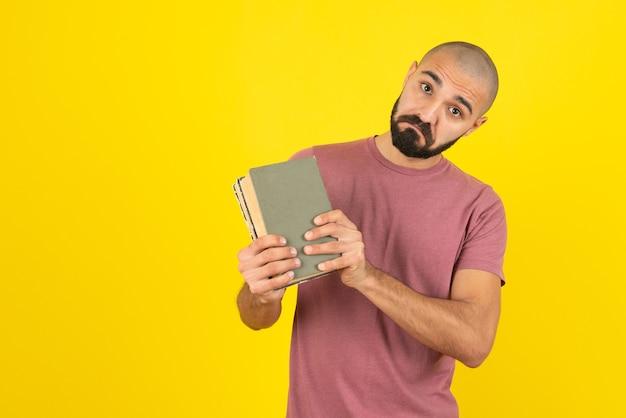 Портрет бородатого мужчины показывает обложку книги над желтой стеной.