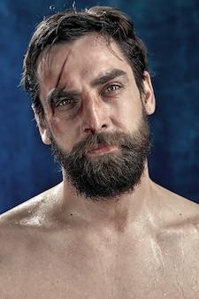 Портрет бородатого мужчины с рассеченной бровью и лбом