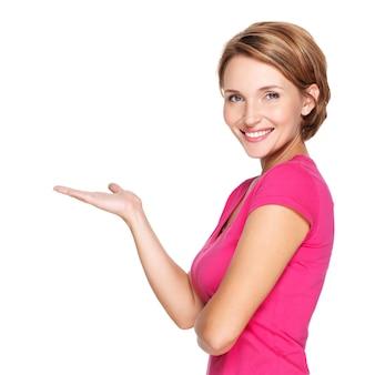 白い壁の上のプレゼンテーションジェスチャーで美しい大人の幸せな女性の肖像画