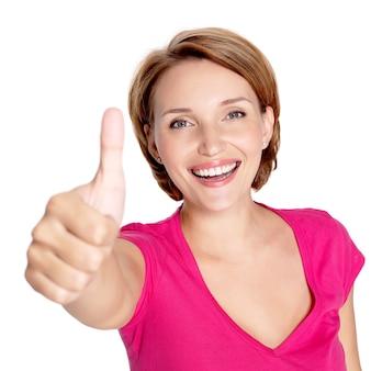 Портрет красивой взрослой счастливой женщины с большими пальцами руки вверх подписывает над белой стеной