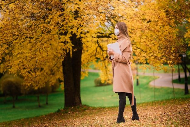 医療フェイスマスクの公園で秋の背景に美しい大人の若い女性の肖像画