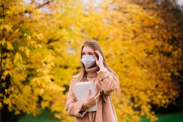 Портрет красивой взрослой молодой женщины на фоне осени в парке в медицинской маске