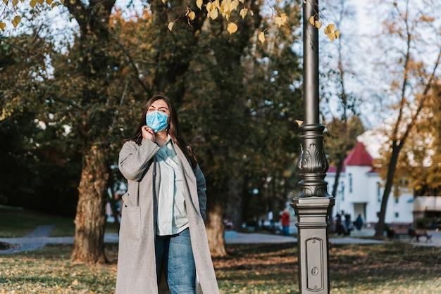 医療用フェイスマスクで公園で秋の背景に美しい大人の若い女性の肖像画